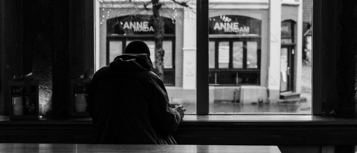 Black and white image. Man sat in window of coffee shop looking out at street.