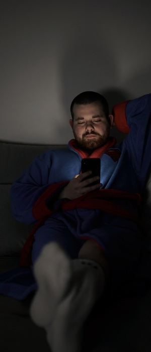 A man sits alone in the dark, watching videos on his phone