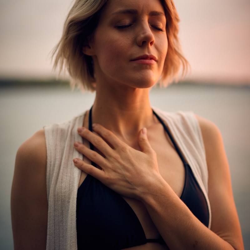 A woman breathes deeply with one hand resting against her collarbone and her eyes closed