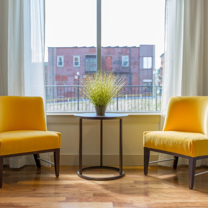 Two yellow chairs are set up facing each other, waiting for a therapy session to begin.
