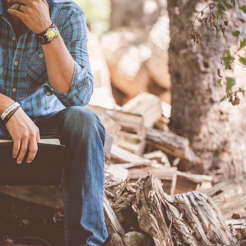 A man sits alone in the woods, resting his chin in his hand, lost in thought.