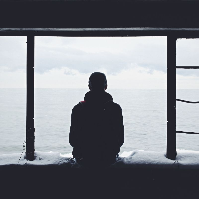 A man stands alone in a window, looking out over an empty sea