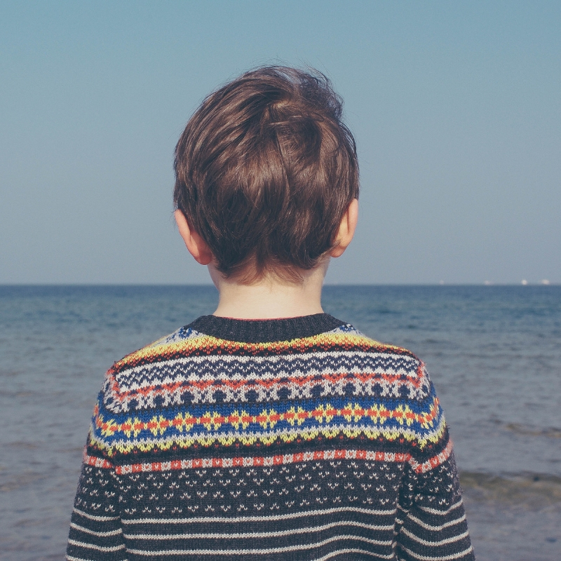 A young boy stares out across the sea