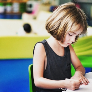 A young child practices writing with crayons