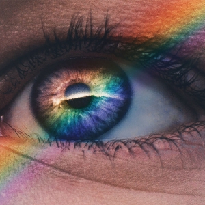 Close-up of an eye with a rainbow reflecting on it