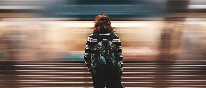 A person stands alone, as a train zips past