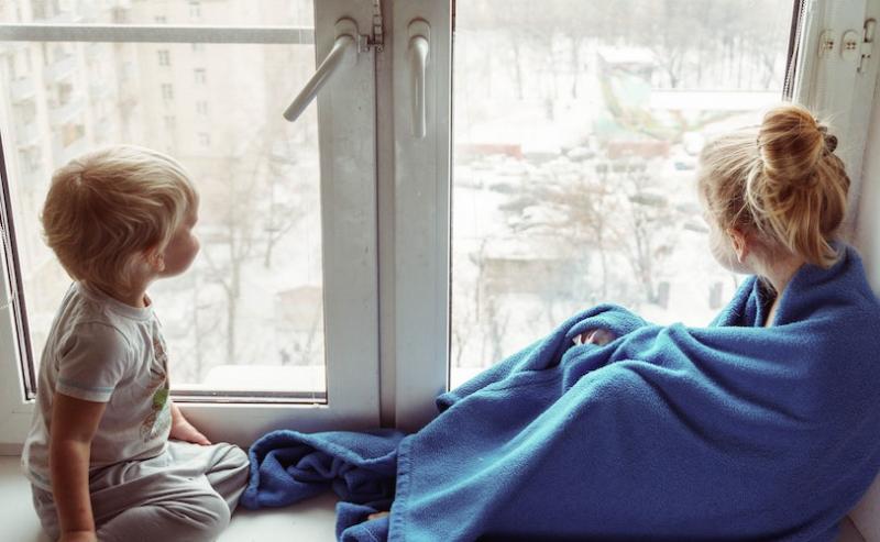 Two children sitting by window