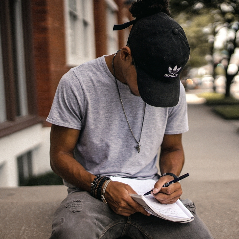 A young man writes in a large notebook, his baseball cap pulled down to cover his face
