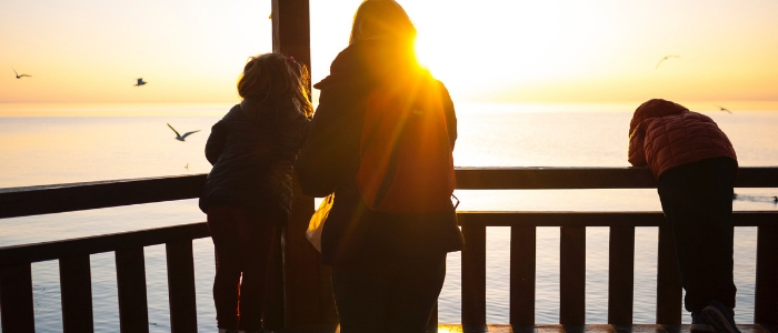 A mother and two children look out over the sea, leaning over wooden railings