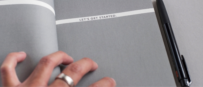 Close-up of a man's hand resting on a notebook, with the words 'let's get started' written on the page.