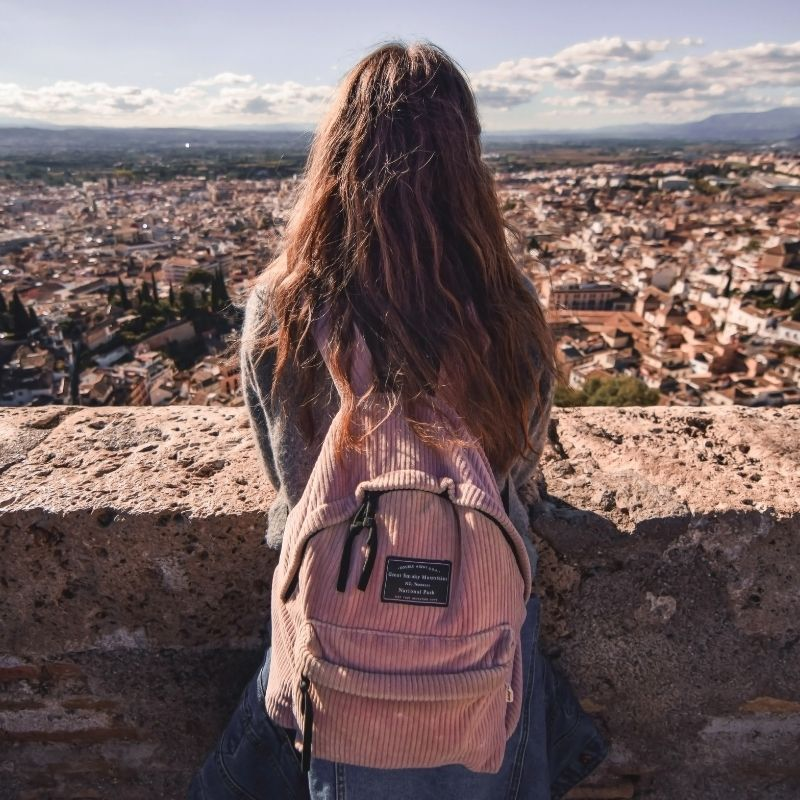 A teenage girl looks out across a city whilst on holiday, mountains in the distance