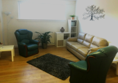 This is a photo of Tranquillo Counselling's comfortable counselling space. There are two green easy chairs and a cream sofa, a grey rug, a plant and a display cabinet.  There is a metal tree on the wall.
