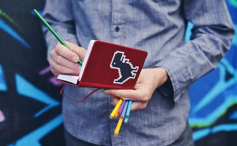 Man holding journal and coloured pencils