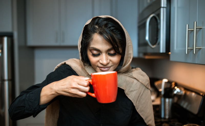 Woman smelling coffee in orange cup