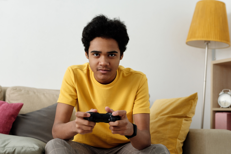 Man in yellow t-shirt playing video games