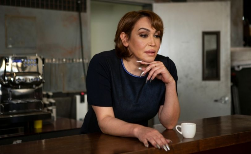 A transgender woman standing at counter