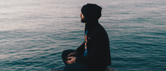 A man meditates outside by water