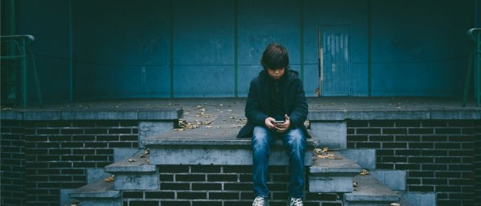 A child sits alone outside, looking down at his mobile with a troubled expression