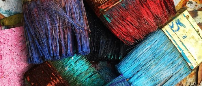A close-up of worn paintbrushes grouped together.