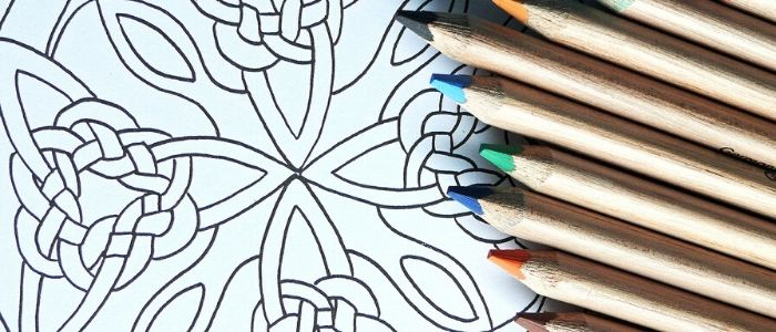 A close-up of colouring pencils and a simple mandala, ready to be coloured in.