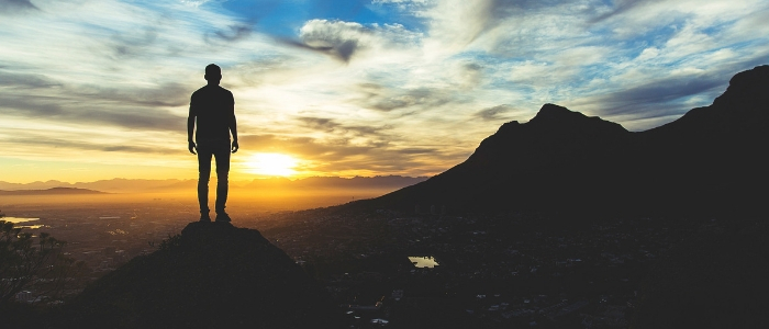 Silhouette of man on mountain against sunset