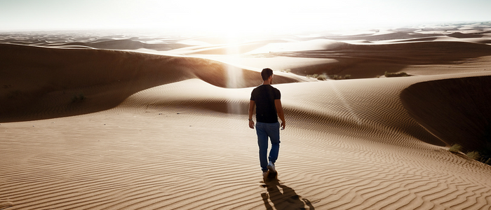 Man walking against sunset on sand