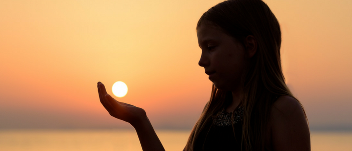 Silhouette of young girl holding the sun