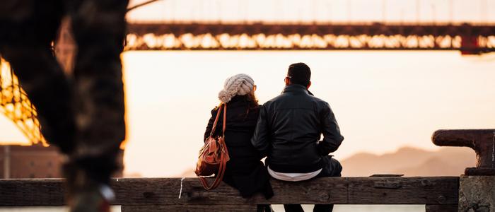 Two people watching sunset on bridge