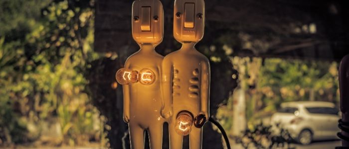 A couple made of light switches stand together in the dark, with their lightbulbs lit up.