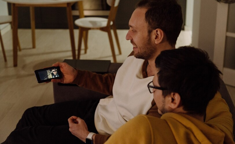Image of two friends watching a video on a phone