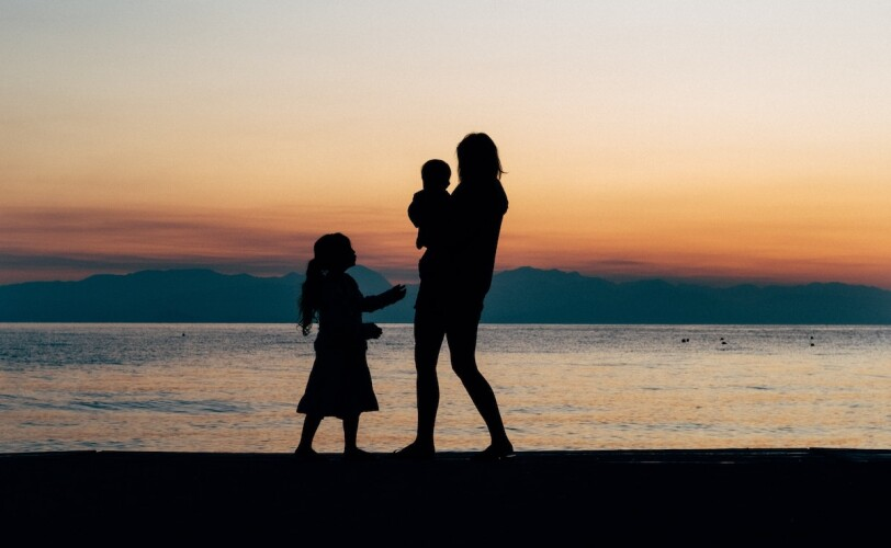 Family standing at the beach at sunset