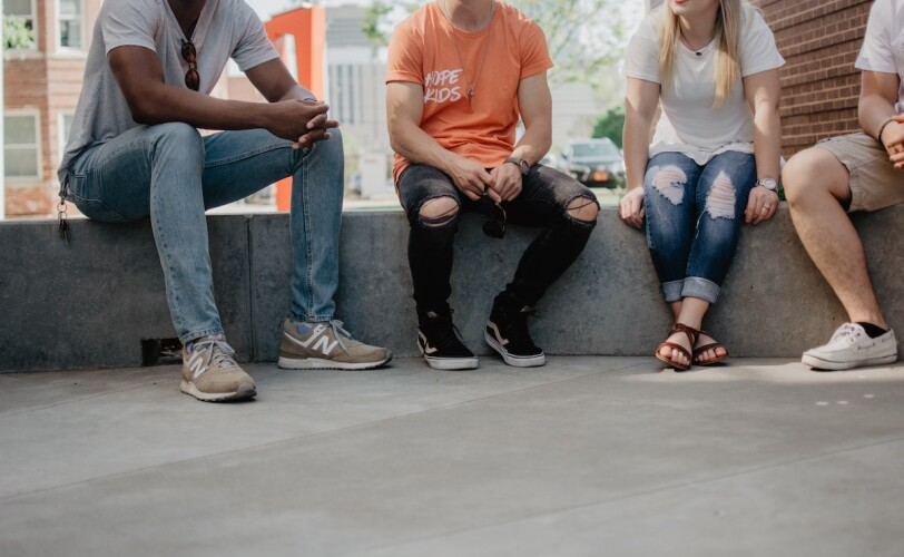Young people sitting together talking