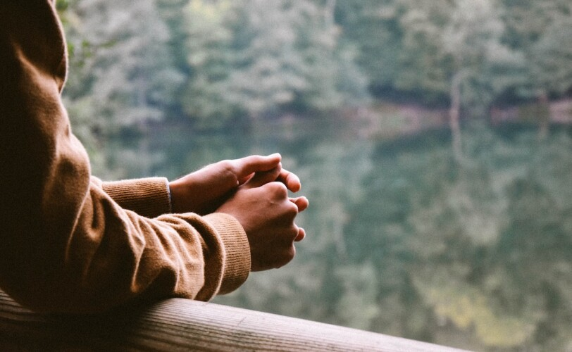 Image of hands leaning on railings looking out to river