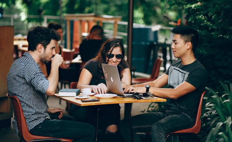 Image of three friends working at an outside coffee shop