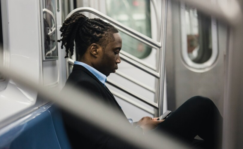 Man on train looking at phone