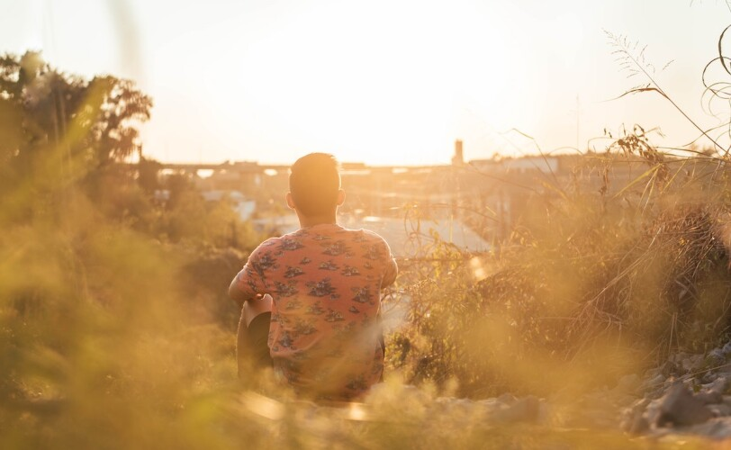 Image of a man sitting in nature looking over the town