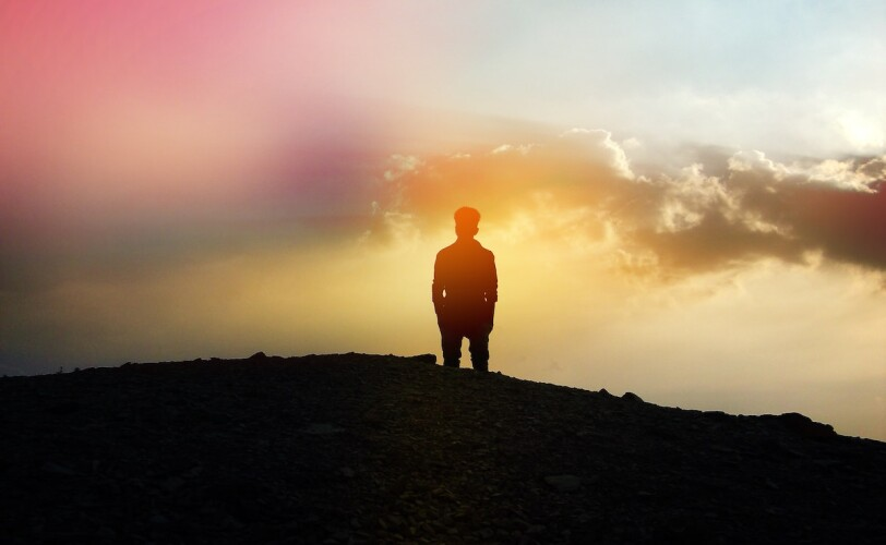 Image of a man standing on a hill amongst a rainbow sunset