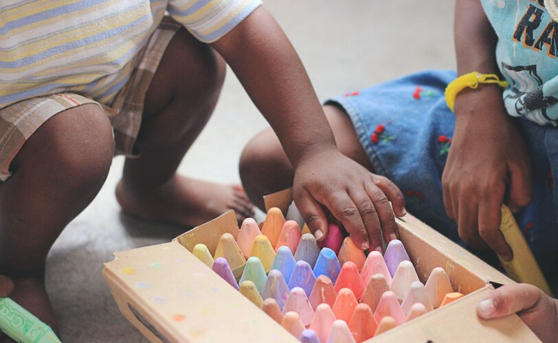 Image of two young children playing with chalk
