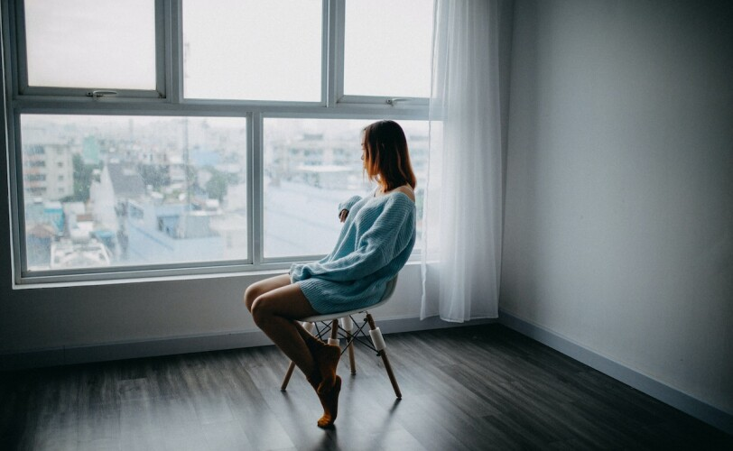 Woman sitting in empty room