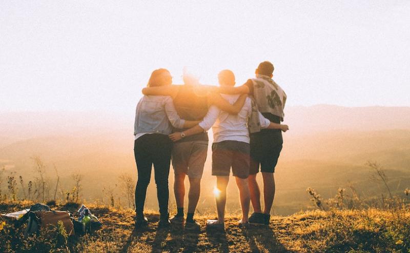 Four friends hug at sunset