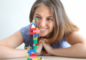 Young Caucasian woman smiling contentedly at a LEGO Serious Play model she has built