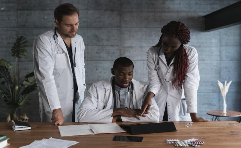 Three doctors around a laptop