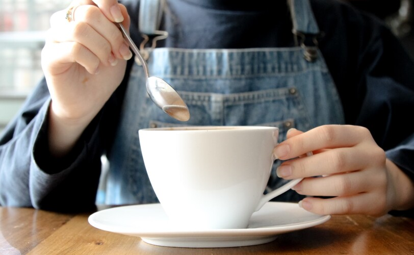 Image of a person stirring a cup of tea