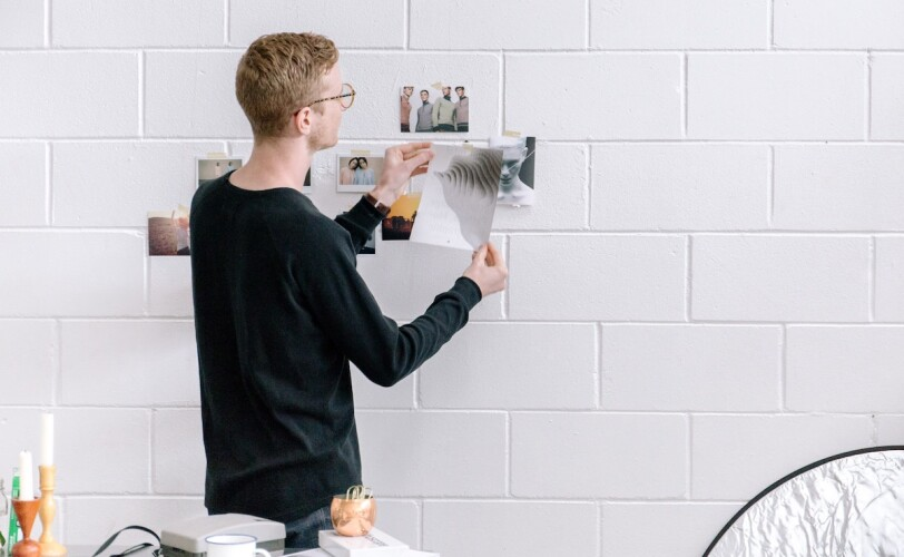 Young man hanging pictures on a wall