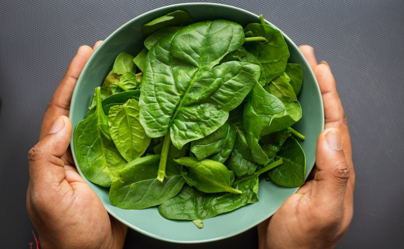 Person holding bowl of spinach