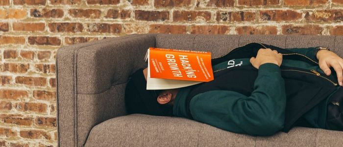 Exhausted man asleep on sofa with book on face