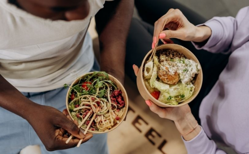 Two friends using chopsticks with bowls of food