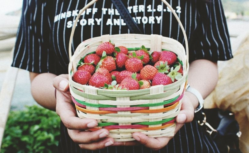 Woman holding basket of strawberries