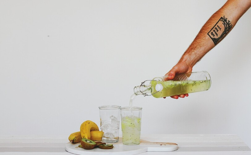 Image of a person pouring green juice into a glass
