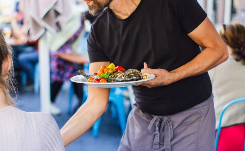 Image of a waiter serving food